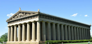 image shows a building similar to Greece's Parthenon with many columns and a frieze.