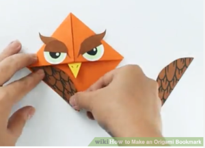 An origami bookmark is decorated to look like an owl.