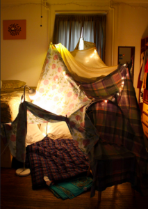 An indoor fort made of hanging sheets, cushions, streaming lights and clothespins.